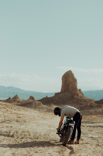 Motorcyclist bending over bike in desert, Trona Pinnacles, California, USの写真素材 [FYI03616917]