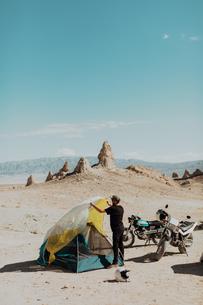 Motorcyclist setting up tent, Trona Pinnacles, California, USの写真素材 [FYI03616920]