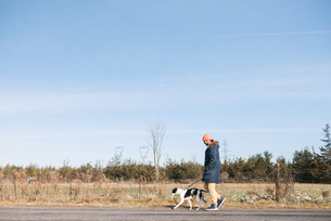 Man walking dog in countrysideの写真素材 [FYI03617075]
