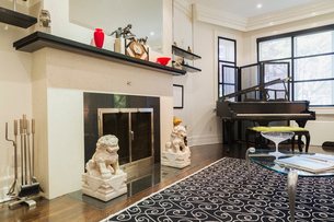 Wood-burning fireplace, grand piano, glass top and silver metal coffee table in living room, wood plの写真素材 [FYI03617129]