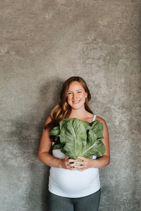 Pregnant woman holding up lettuceの写真素材 [FYI03617160]