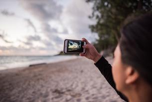 Woman taking photo on Kailua Beach, Oahu, Hawaiiの写真素材 [FYI03617440]