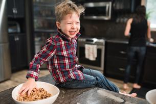 Toddler grabbing freshly baked vegetarian seed balls from bowl on kitchen worktopの写真素材 [FYI03617503]