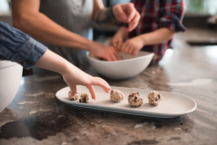 Children enjoying freshly baked vegetarian seed ballsの写真素材 [FYI03617518]