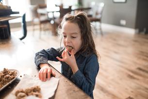 Little girl eating freshly baked vegetarian seed ballの写真素材 [FYI03617520]