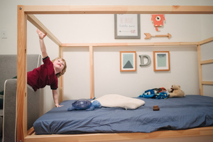 Boy climbing four poster bedの写真素材 [FYI03617531]