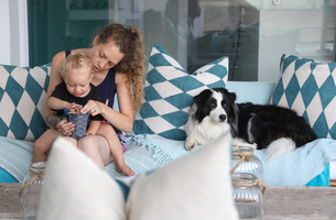 Mother eating snacks with baby son on patio sofaの写真素材 [FYI03617651]