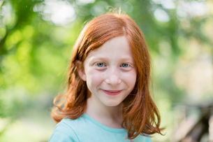 Red haired girl in garden, head and shoulder portraitの写真素材 [FYI03617687]