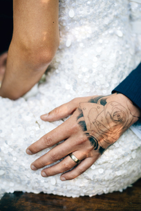 Groom's tattooed hand on bride's hip, mid sectionの写真素材 [FYI03617731]
