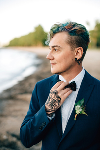 Bridegroom with hand tattoo looking out from lakesideの写真素材 [FYI03617747]