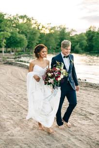 Romantic bride and groom strolling barefoot on lakeside, Lake Ontario, Toronto, Canadaの写真素材 [FYI03617752]
