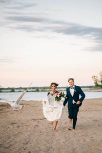 Romantic bride and groom running barefoot on lakeside, Lake Ontario, Toronto, Canadaの写真素材 [FYI03617755]