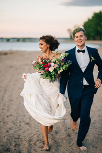 Bride and groom running barefoot on lakeside, Lake Ontario, Toronto, Canadaの写真素材 [FYI03617756]