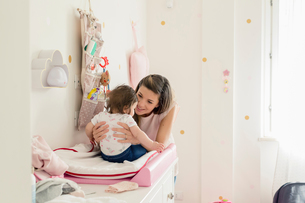 Mother talking to baby girl on changing tableの写真素材 [FYI03617766]