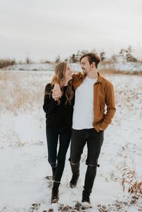 Happy couple enjoying walk in snowy fieldの写真素材 [FYI03617845]