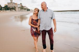 Couple taking walk on beach, Estoril, Lisboa, Portugalの写真素材 [FYI03617868]