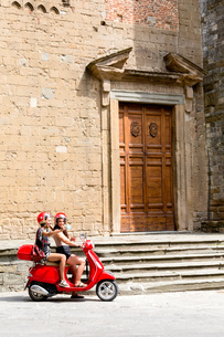 Friends taking selfie on scooter by church entrance, Citt・della Pieve, Umbria, Italyの写真素材 [FYI03618002]