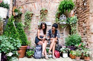 Friends enjoying peaceful corner with plants, Citt・della Pieve, Umbria, Italyの写真素材 [FYI03618008]