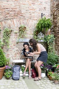 Friends enjoying peaceful corner with plants, Citt・della Pieve, Umbria, Italyの写真素材 [FYI03618010]