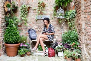 Woman enjoying peaceful corner with plants, Citt・della Pieve, Umbria, Italyの写真素材 [FYI03618011]