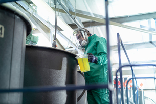 Worker pouring chemical into mixing tanks in chemical factoryの写真素材 [FYI03618037]