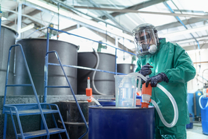 Worker filling jug with chemical in chemical factoryの写真素材 [FYI03618038]