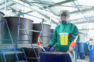 Worker with jug of chemical in chemical factoryの写真素材 [FYI03618039]