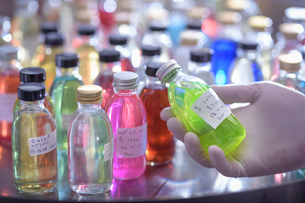 Hand holding sample product bottle in chemical factoryの写真素材 [FYI03618052]