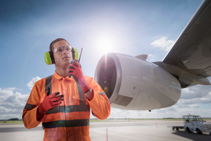 Composite image of airport worker speaking on walkie talkie in front of A380 engineの写真素材 [FYI03618079]