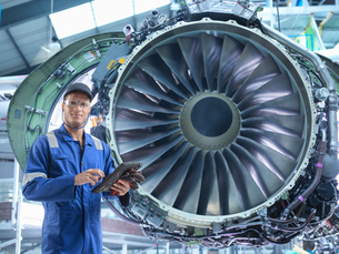 Composite image of engineer with jet engine in aircraft maintenance factoryの写真素材 [FYI03618086]