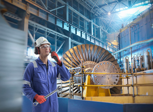 Composite image of engineer with walkie talkie in power stationの写真素材 [FYI03618087]