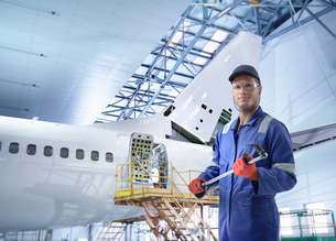 Composite image of engineer with wrench tool in aircraft maintenance factoryの写真素材 [FYI03618090]