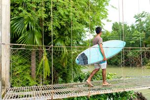 Man with surfboard on rope bridge, Pagudpud, Ilocos Norte, Philippinesの写真素材 [FYI03618141]