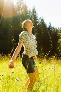 Woman dancing amongst wild flowers in forest, Sonthofen, Bayern, Germanyの写真素材 [FYI03618226]
