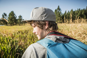 Teenage boy with backpack in field of long grass, Sandpoint, Idaho, USAの写真素材 [FYI03618257]