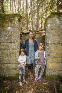 Woman and two daughters standing in derelict doorway in forest, Sandpoint, Idaho, USAの写真素材 [FYI03618260]