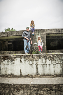 Senior man and two granddaughters standing on derelict structure, portrait, Port Townsend, Washingtoの写真素材 [FYI03618261]