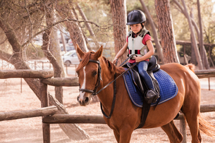 Girl learning to ride horse in paddockの写真素材 [FYI03618280]