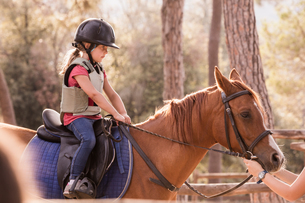 Girl learning to ride horse in paddockの写真素材 [FYI03618283]
