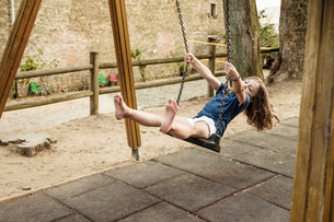 Barefoot girl on playground swing, Portoferraio, Tuscany, Italyの写真素材 [FYI03618297]