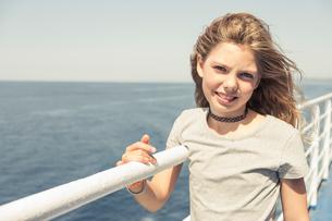 Blond haired girl on windy pier, portrait, Portoferraio, Tuscany, Italyの写真素材 [FYI03618300]