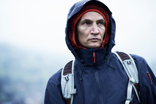 Mature male hiker in hooded anorak in rain, Manigod, Rhone-Alpes, Franceの写真素材 [FYI03618540]
