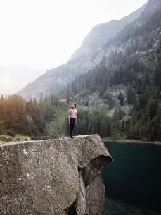 Woman enjoying view by lake, Antronapiana, Piemonte, Italyの写真素材 [FYI03618792]