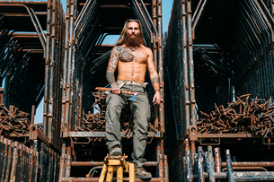 Man with axe by steel storageの写真素材 [FYI03618870]