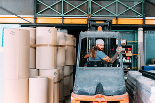 Man reversing fork lift out of warehouseの写真素材 [FYI03618874]