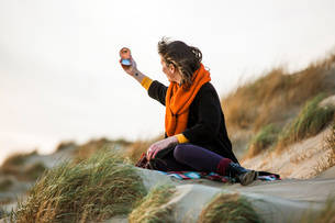 Woman looking at compact mirror on beachの写真素材 [FYI03618894]