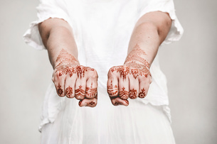 Woman in white dress with henna tattoo on fistsの写真素材 [FYI03618902]