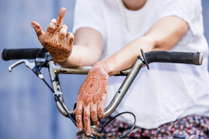 Woman with henna tattoo on hands sitting on bicycle making rude gestureの写真素材 [FYI03618909]