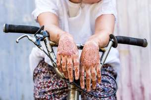 Woman with henna tattoo on hands sitting on bicycleの写真素材 [FYI03618911]