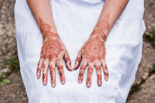 Woman in white dress with henna tattoo on handsの写真素材 [FYI03618913]